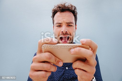 istock Excited young man looking towards a cell phone 521982620