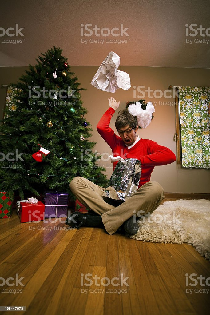 Excited young man on Christmas morning opening gifts stock photo