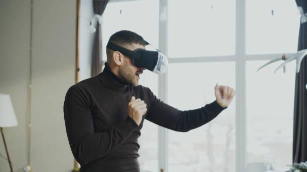 jungen mann mit virtual reality kopfhörer tanzen und spielen 360 video spiel zu hause begeistert - free online game stock-fotos und bilder