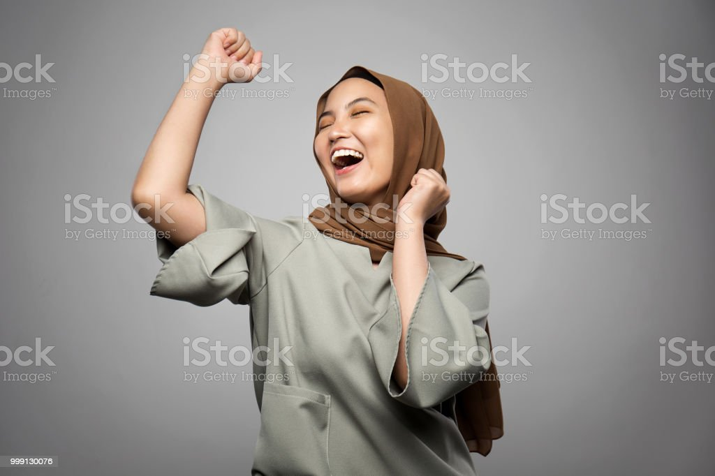 Excited young Muslim woman in white background stock photo