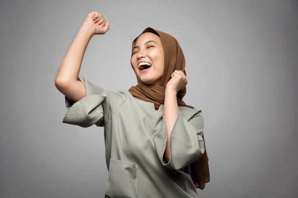 excited young muslim woman in white background - hijab foto e immagini stock