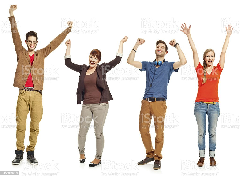 Excited young people Four happy young adults standing with raised hands and laughing at the camera. Studio shot, white background. 18-19 Years Stock Photo