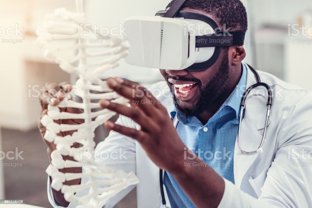 Excited young practitioner in virtual reality glasses touching DNA model stock photo