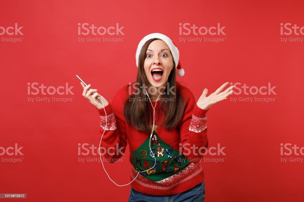 Excited young Santa girl with earphones keeping mouth wide open,...