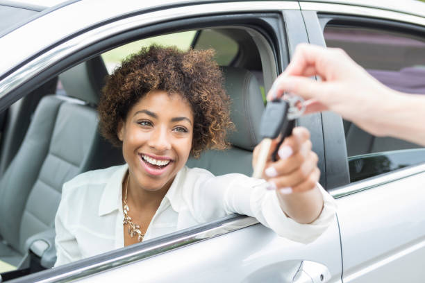 excited young woman accepts new car keys - used car selling stock pictures, royalty-free photos & images