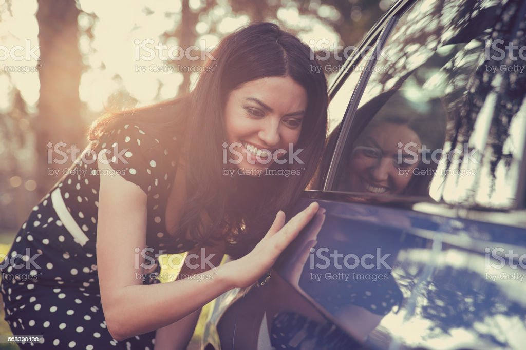 Excited young woman and her new car outdoors with sunlit forest in background. stock photo