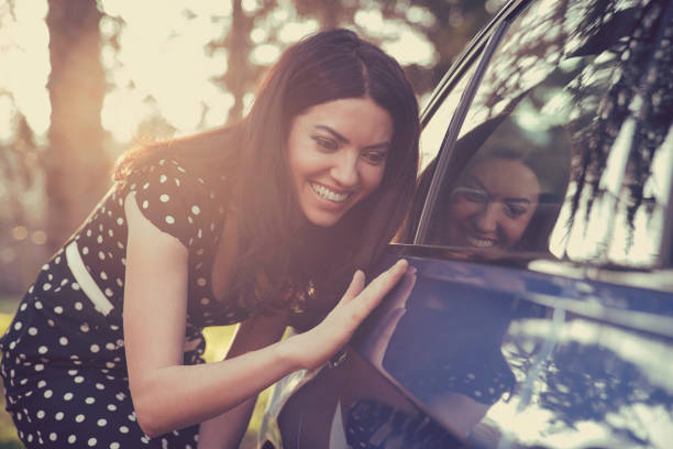 excited young woman and her new car outdoors with sunlit forest in background. - new stock photos and pictures