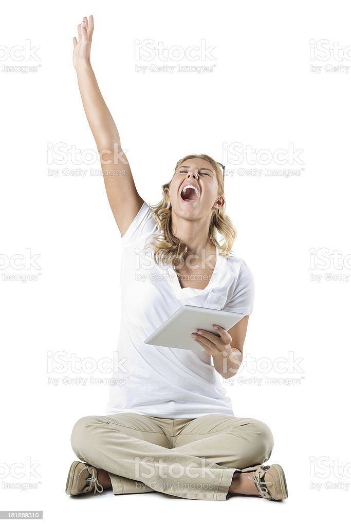 Excited young woman cheering while holding digital tablet; studio shot royalty-free stock photo
