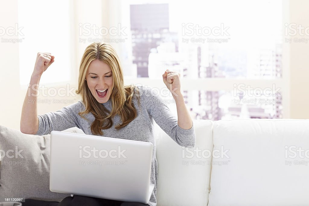 Excited young woman cheering while looking at laptop royalty-free stock photo