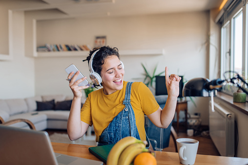 Young woman listening to the music and enjoying at home after work.