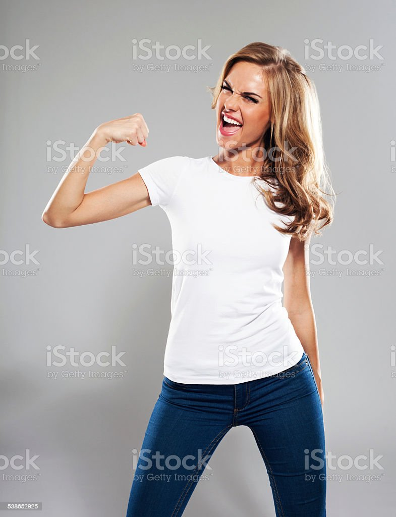 Excited young woman flexing her bicep, Studio Portrait stock photo