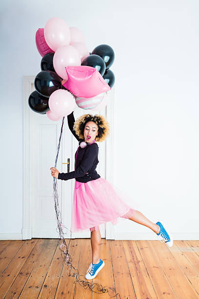 excited young woman holding bunch of balloons indoors - damen rock pink stock-fotos und bilder