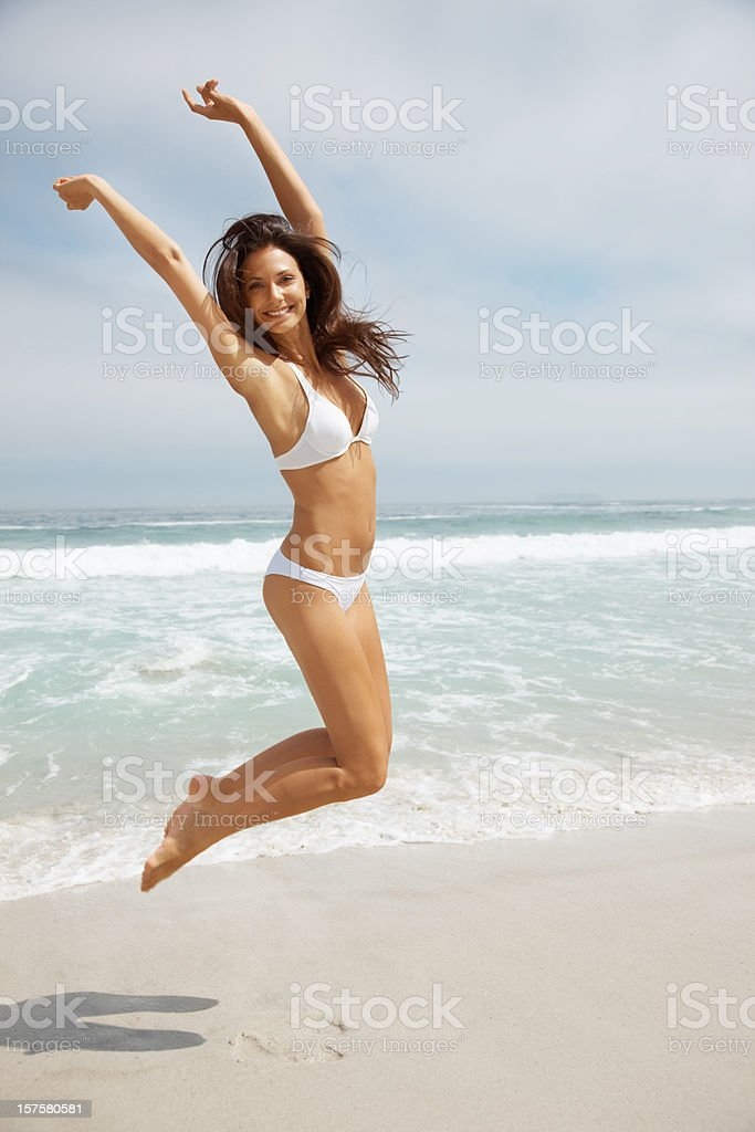Excited young woman in bikini jumping mid air stock photo
