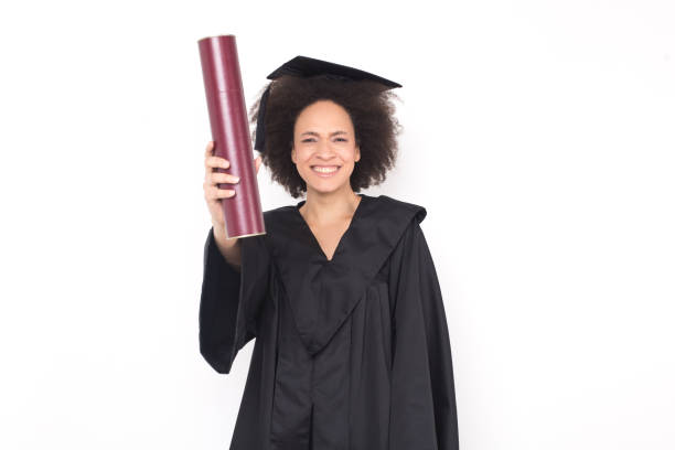 e1aa0ca69c9 Excited young woman in graduation gown holding diploma stock photo