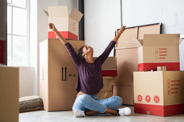 Excited young woman in new house Happy young woman sitting in new apartment and raising arms in joy after moving in. Joyful and excited african girl moving to new home. Black woman sitting on floor in her house. home ownership stock pictures, royalty-free photos & images
