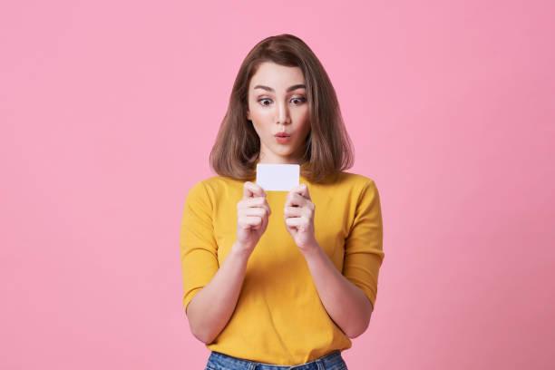 aufgeregtjunge Frau in gelbem Hemd zeigt Kreditkarte isoliert über rosa Hintergrund. – Foto
