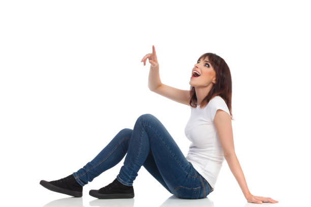 excited young woman is sitting on floor, pointing, looking up and shouting. side view - sitting on floor stock photos and pictures