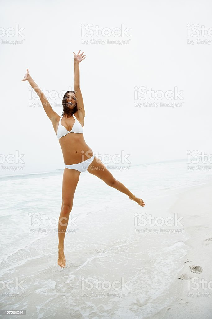 Excited young woman jumping in joy on the beach stock photo