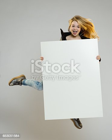 istock Excited young woman jumping with a blank poster 653051584