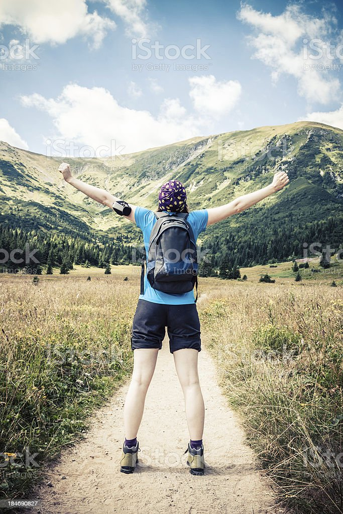 Excited young woman on a mountain hiking trail royalty-free stock photo