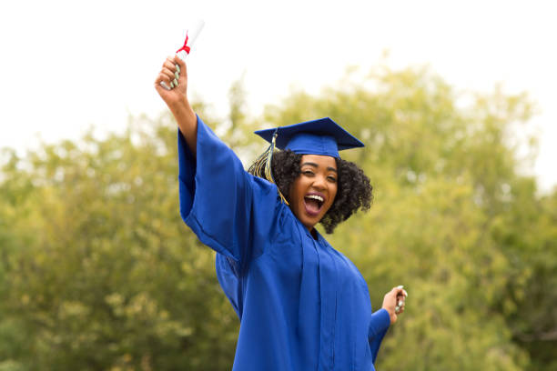 Excited young woman on graduation day. stock photo