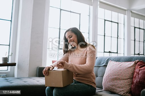 A cheerful Hispanic woman sits in her home living room opening a cardboard box package from an online delivery.