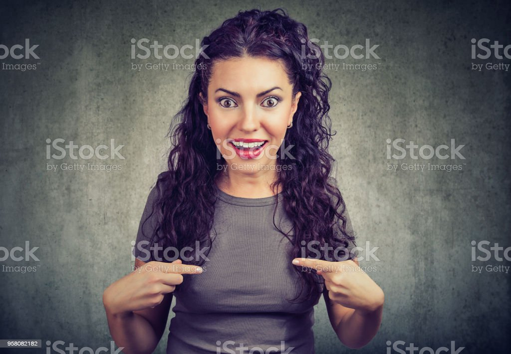 Excited young woman pointing at herself in disbelief of being winner stock photo
