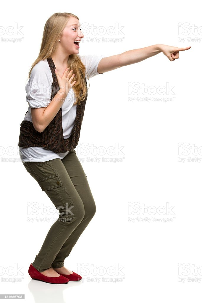 Excited Young Woman Points to the Side royalty-free stock photo