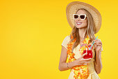 istock Excited young woman posing isolated over yellow background dressed in dress and drinking cocktail 1202301916