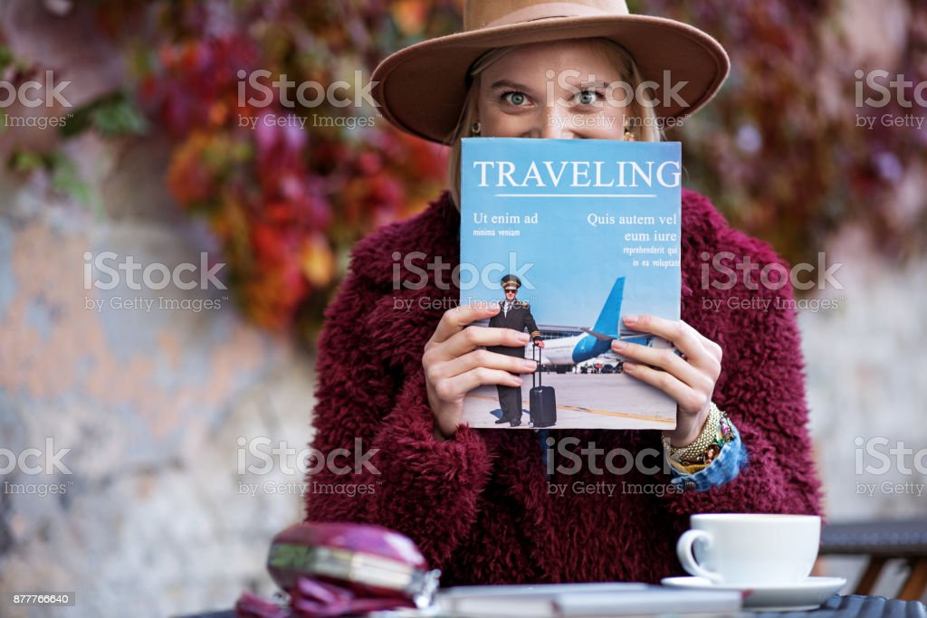 Excited young woman reading journal about journeys stock photo
