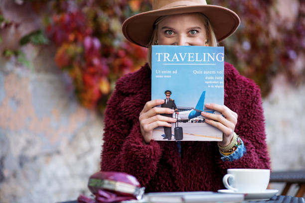 excited young woman reading journal about journeys - magazine stock photos and pictures