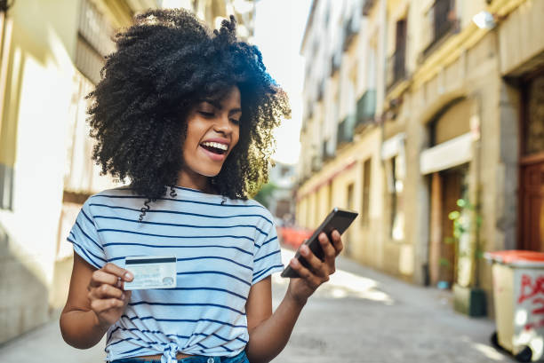 Excited young woman walking and shopping online stock photo