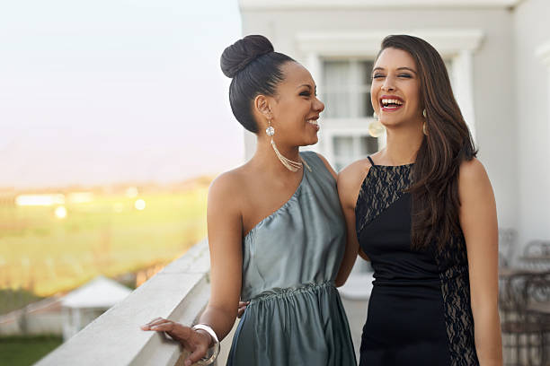Excitement before the prom Two young women in evening wear standing on a balcony evening wear stock pictures, royalty-free photos & images