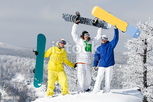 Portrait of three successful snowboarders raising their arms     Note to inspector: the image is pre-Sept 1 2009