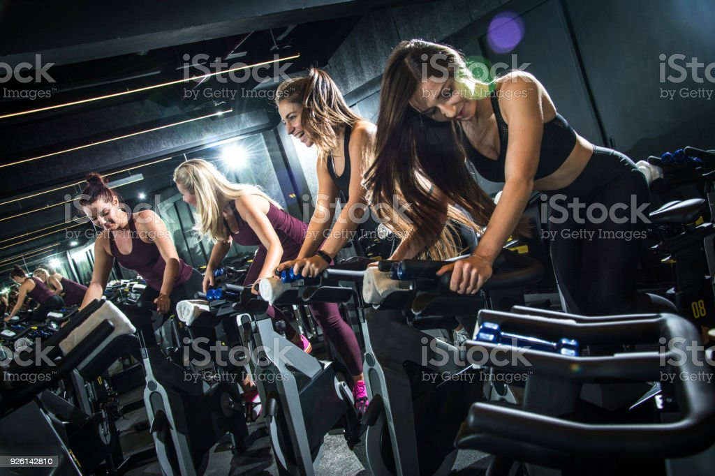 Excitement sporty young women on cycling class. stock photo
