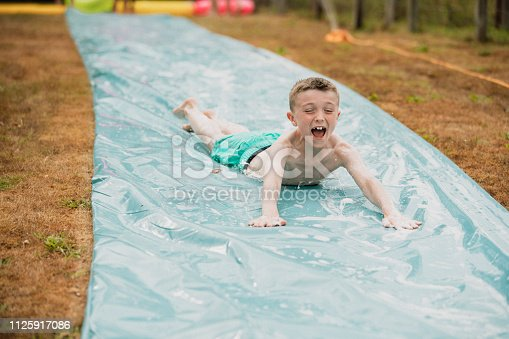 A front view shot of a young boy sliding down a water slide on his stomach in a garden, he is having a fun time.