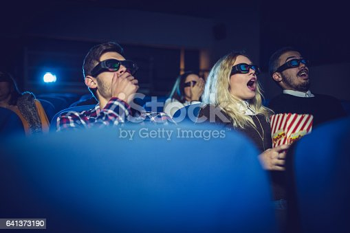 Group of people, watching action movie in cinema.