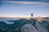 A climber reaches the summit of an exposed mountain top in the Tahoe backcountry, California
