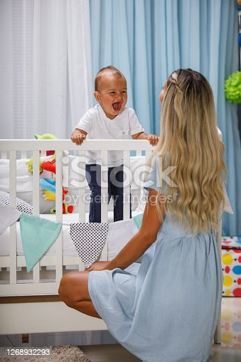 Rear view of mother with long blond hair and blue dress kneeling in front of baby's white crib. The baby boy smiles and screams excitedly.