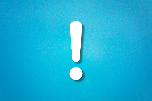 istock Exclamation mark on blue background 1169898351