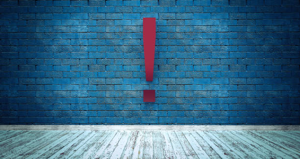 Exclamation mark symbol on blue brick wall stock photo