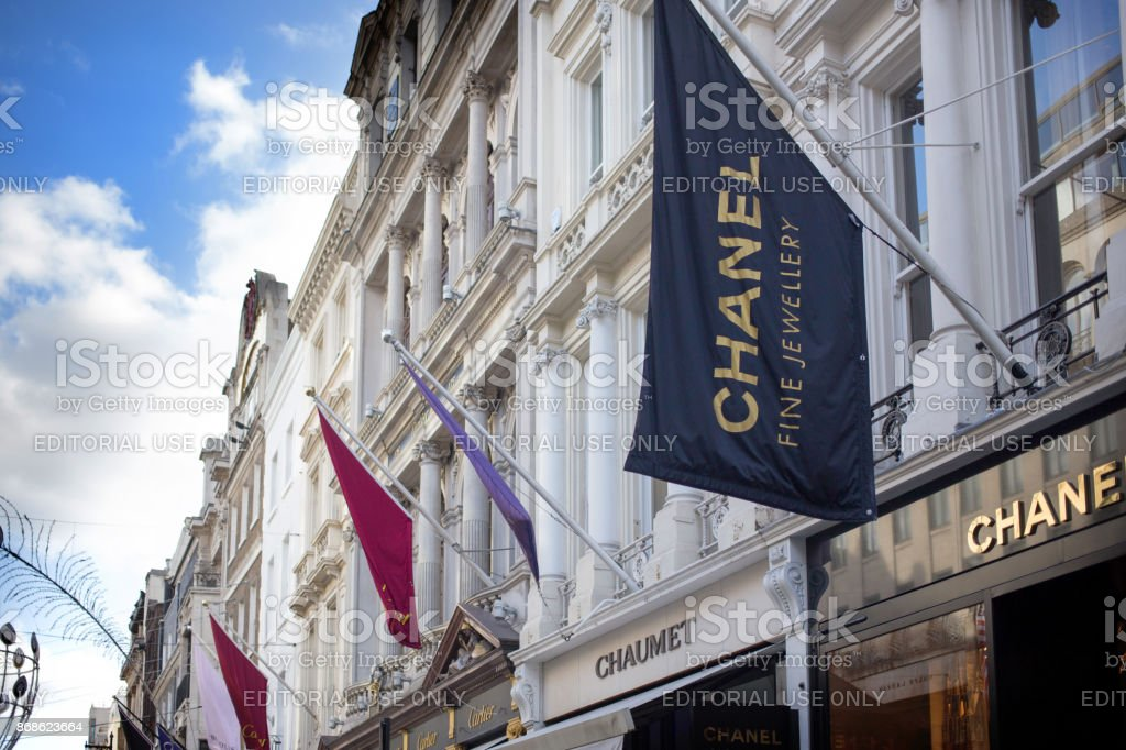 Exclusive shopping in New Bond Street. Showing store flags for Chanel, Chamet and Cartier. High end shops for jewellery, watches and fashion
