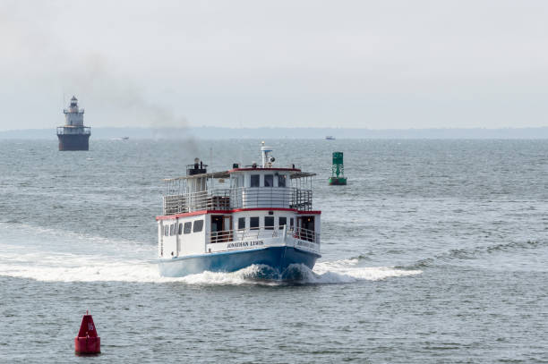 excursion boat jonathan lewis with lighthouse in background - john lewis стоковые фото и изображения