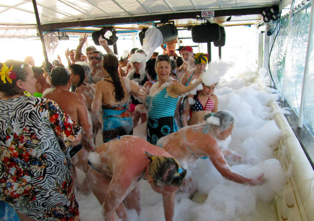 Excursion, boat trip. Foam party on a sea boat, people dance in the foam stock photo