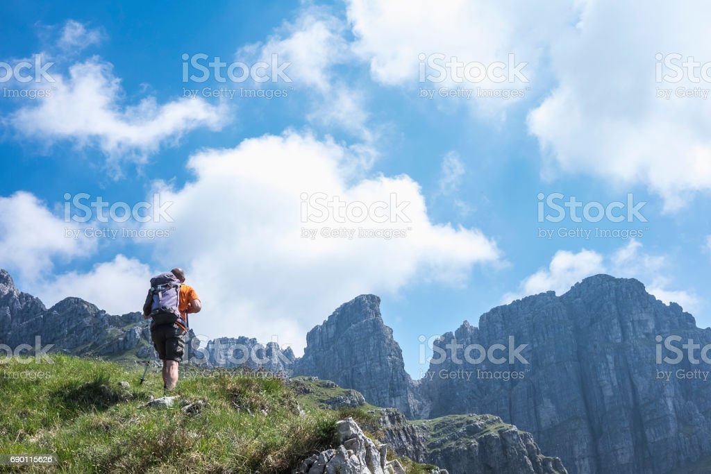 Excursionist walking along high mountain path stock photo