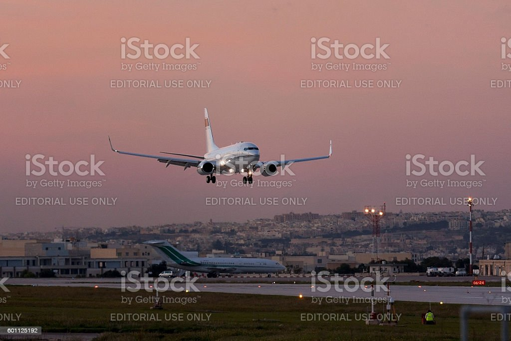 Executive 737-BBJ landing after sunset. stock photo