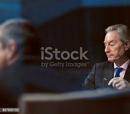 637940820 istock photo Executive businessman looking at notes in meeting 637933152