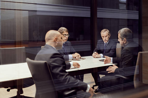 Executive businessmen talking in meeting room Executive businessmen talking in meeting room governing board stock pictures, royalty-free photos & images