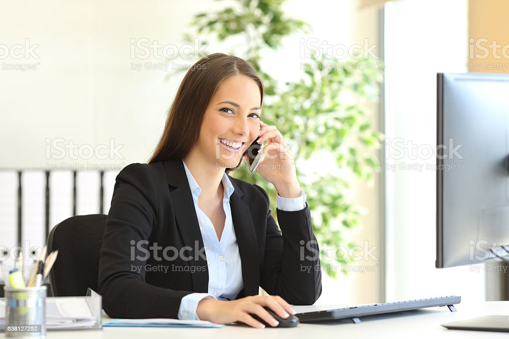 Executive calling on phone and looking at camera stock photo