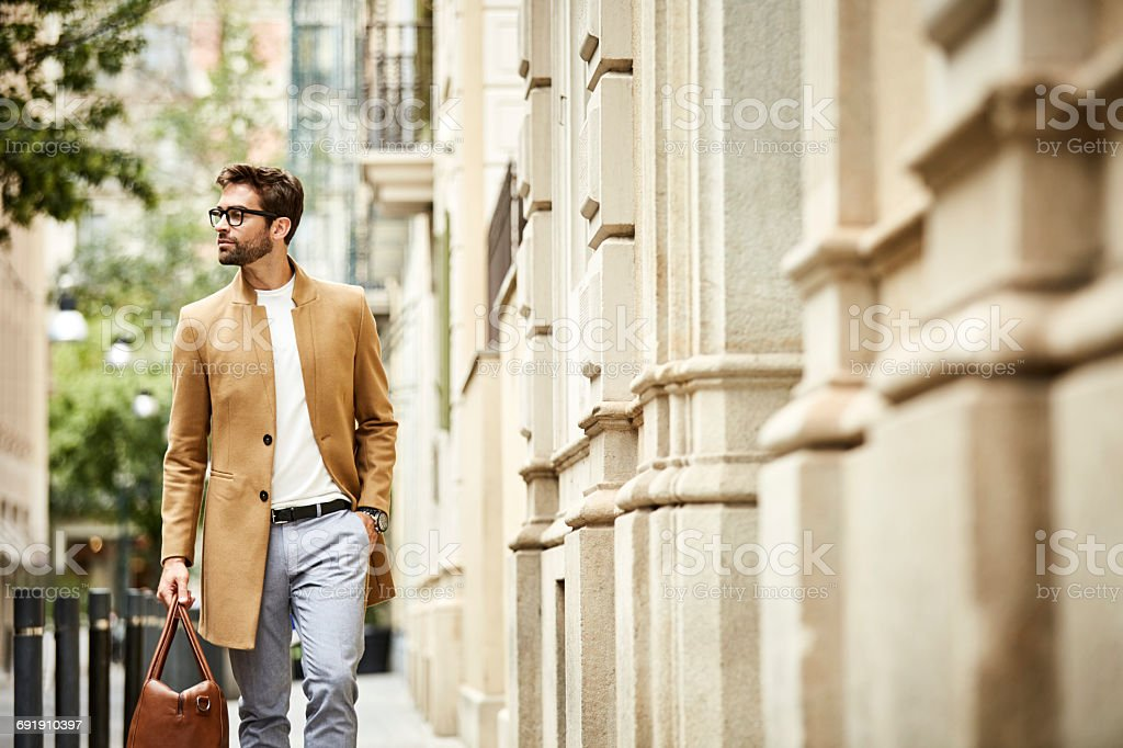 Executive carrying bag with hand in pocket at city - foto de acervo